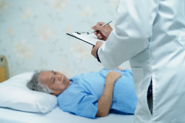 Médecin notant le diagnostic sur le presse-papiers pendant que la patiente senior allongée sur le lit à l'hôpital