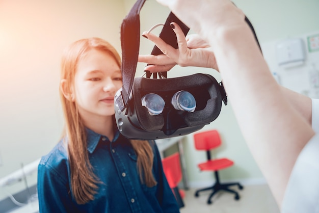 Un médecin en ophtalmologie vérifie la vision de la fille à l'aide de lunettes de réalité virtuelle.
