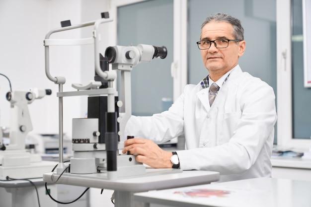 Médecin ophtalmologiste posant avec lampe à fente dans l'armoire.