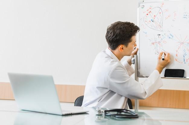 Médecin avec ordinateur portable écrit sur tableau blanc