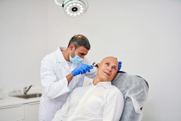 Médecin orl vérifiant l'oreille avec otoscope à l'homme patient à l'hôpital
