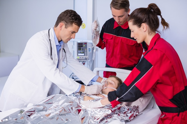 Médecin et paramédical examinant un patient en salle d'urgence