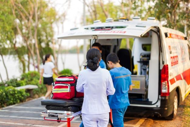 Médecin paramédical d'urgence et infirmière debout à l'arrière de l'ambulance