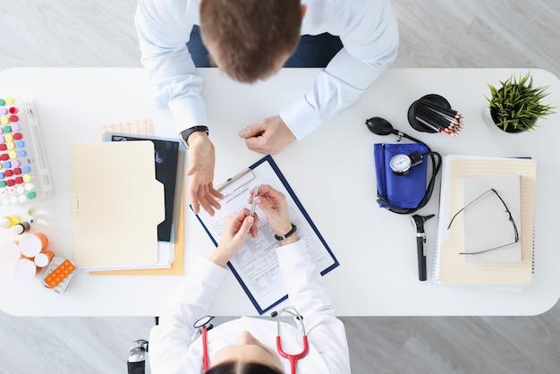 Médecin parlant au patient en vue de dessus de bureau. collection du concept d'histoire médicale