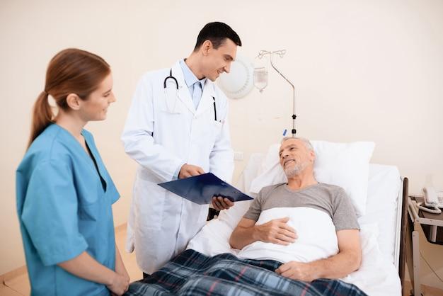Un médecin parle à un patient dans son lit d'hôpital.