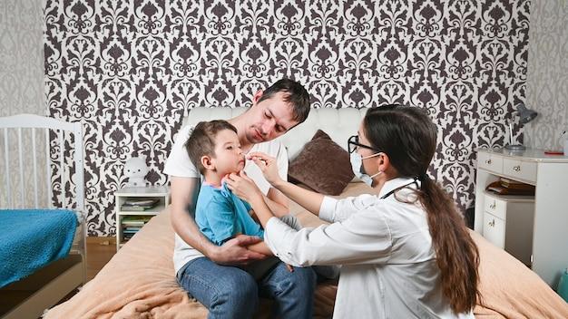 Un médecin passe un test de coronavirus sur un enfant à la maison.