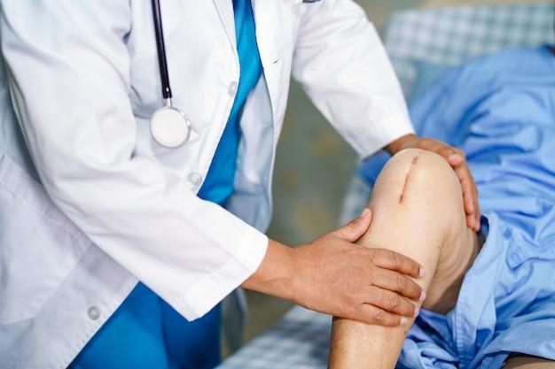 Médecin, patient asiatique senior, cicatrices, arthroplastie totale du genou.