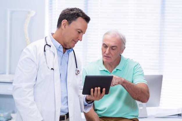 Médecin et patient senior à l'aide de tablette numérique