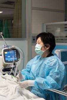 Médecin patient de soins médicaux sur le lit à l'hôpital