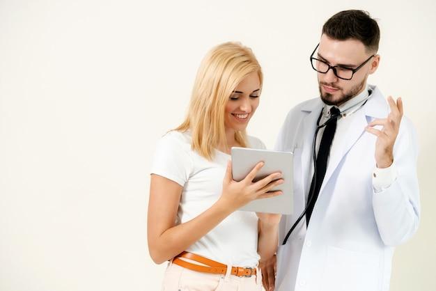 Un médecin et une patiente regardent un ordinateur tablette pour un enregistrement de données de santé.