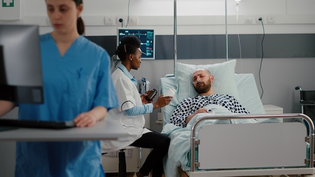 Médecin à la peau foncée expliquant le traitement par pilules contre la douleur lors d'un examen médical en salle d'hôpital. patient malade avec tube à oxygène assis dans son lit pendant que le médecin tape son expertise en matière de santé