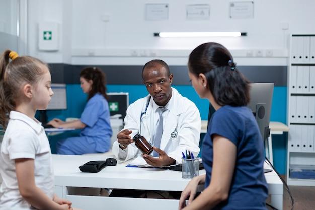 Médecin pédiatre afro-américain expliquant le traitement médicamenteux
