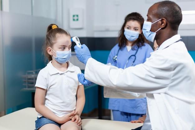 Médecin pédiatre afro-américain avec masque facial contre le coronavirus