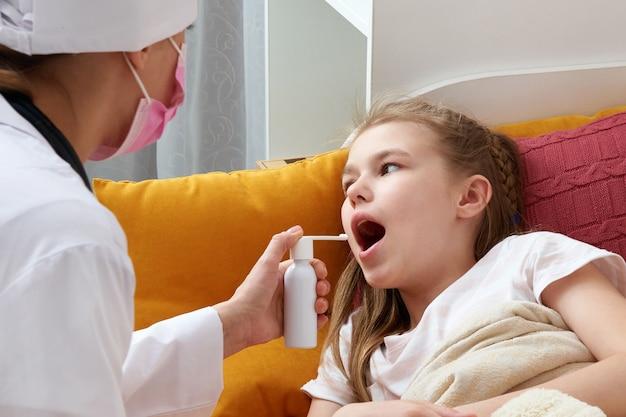 Médecin pédiatre à l'aide d'un spray médical pour jeune fille à la maison, mal de gorge