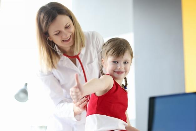 Médecin pédiatre écoute le souffle de la petite fille à travers un stéthoscope