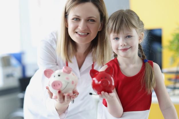 Un médecin pédiatre et une petite fille tiennent une tirelire cochon. concept d'assurance-maladie pour enfants
