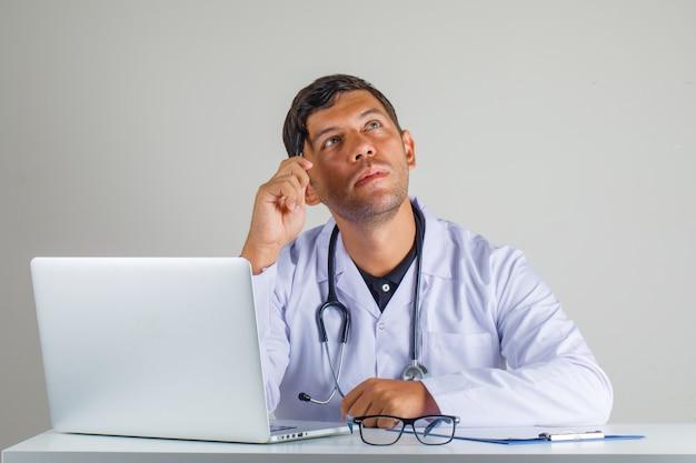 Médecin pensant et regardant loin en blouse blanche, stéthoscope et regardant contemplatif