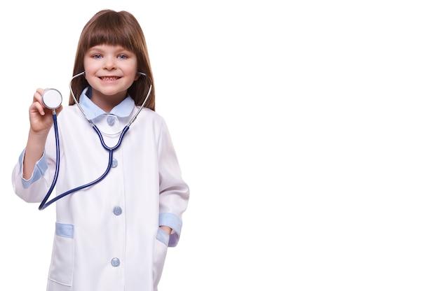 Médecin de petite fille souriante mignonne portant un blouse blanche tient un stéthoscope sur fond blanc isolé