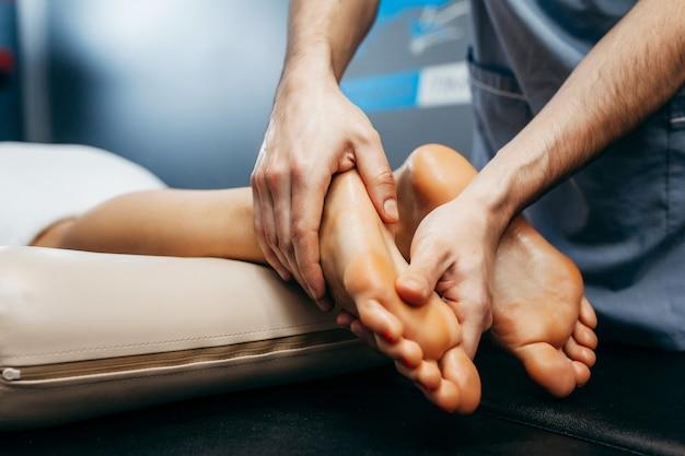 Le médecin-podiatre effectue un examen et un massage du pied du patient à la clinique.