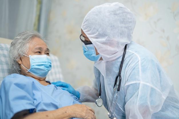 Un médecin portant un costume en ppe pour vérifier une patiente âgée asiatique pour protéger l'infection covid coronavirus