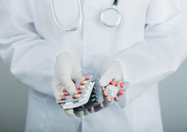 Médecin portant des gants en latex transparent tenant pile de pilules différentes sur le mur gris de l'hôpital. antibiotiques et comprimés de traitement viral.