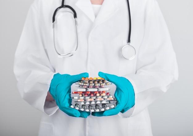 Médecin portant des gants en latex vert tenant pile de différentes pilules, antibiotiques et comprimés de traitement de virus sur le mur gris de l'hôpital.