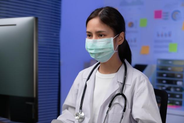 Le médecin portant un masque est assis à un bureau la nuit.