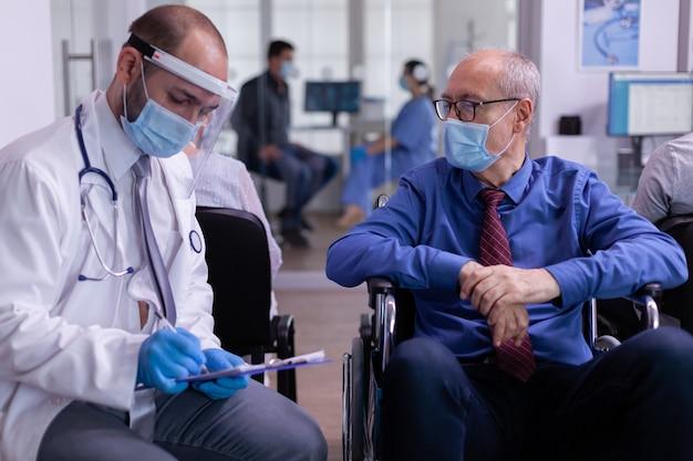 Médecin portant un masque facial et une visière contre l'infection par le coronavirus parlant avec un homme âgé handicapé dans la salle d'attente assis sur un fauteuil roulant