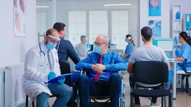 Médecin portant un masque facial et une visière contre l'infection par le coronavirus tout en parlant avec un homme âgé handicapé dans la zone d'attente assis sur un fauteuil roulant. patient et infirmière à la réception de la clinique.