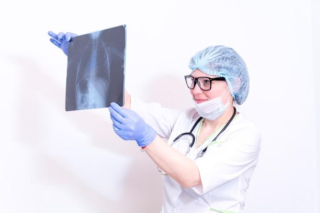 Un médecin portant un masque de protection et des gants médicaux bleus se penche sur une radiographie pulmonaire