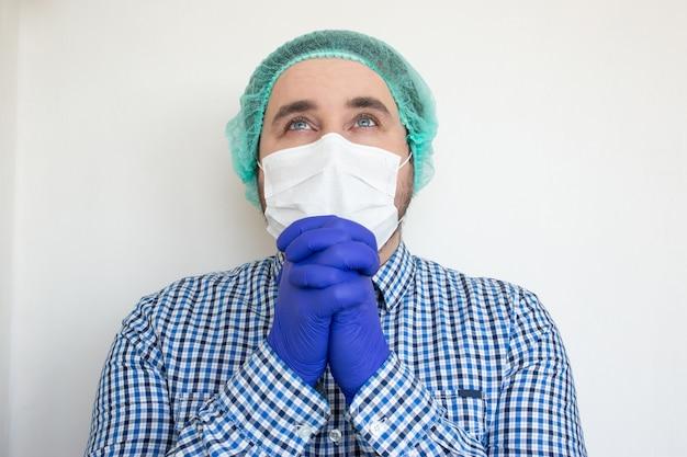 Un médecin portant un masque de protection prie. inspirer confiance en l'avenir pour résoudre la crise.
