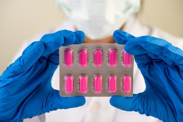 Le médecin porte des gants et tient des panneaux de médicaments.