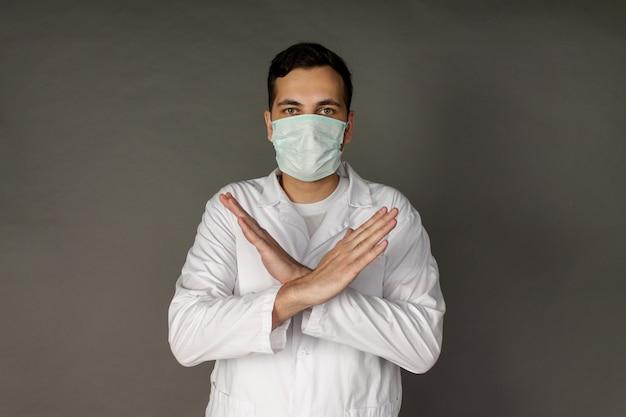 Un médecin porte un masque pour se protéger du coronavirus et croise les bras