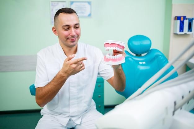 Médecin positif en uniforme blanc montrant une mâchoire simulée avec des dents alors qu'il était assis dans un cabinet dentaire