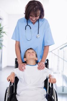 Médecin poussant un garçon handicapé dans le couloir de l'hôpital