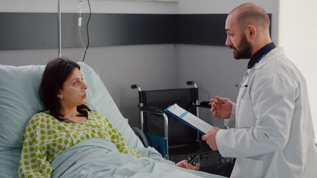 Médecin praticien écrivant une expertise de test sur le presse-papiers surveillant le diagnostic de la maladie travaillant dans la salle d'hôpital. patient malade se reposant dans son lit parlant du traitement de la maladie pendant la convalescence médicale