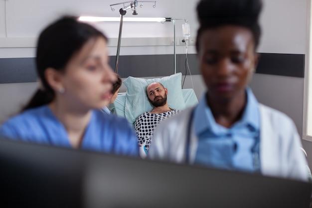 Médecin praticien à la peau noire parlant avec une femme assistante lors d'une consultation médicale