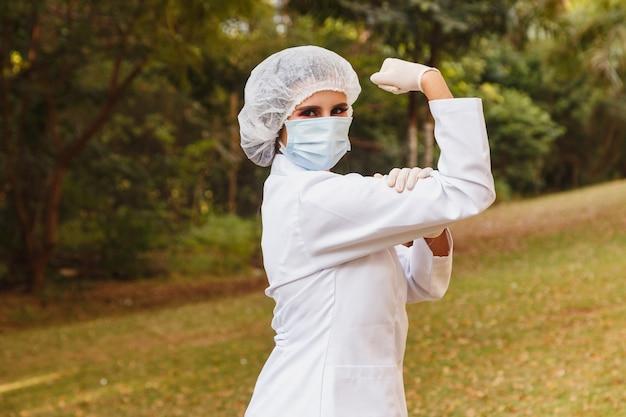 Médecin de première ligne faisant le symbole de l'autonomisation ou du militantisme des femmes