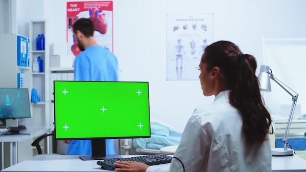 Médecin prenant des notes sur ordinateur avec écran vert chroma key et infirmière en uniforme bleu dans une armoire d'hôpital. medic en blouse blanche travaillant sur un moniteur avec un espace vide dans l'armoire de la clinique pour vérifier le patient d