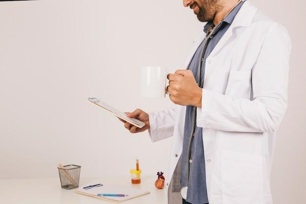 Le médecin prend du café et travaille avec l'ipad