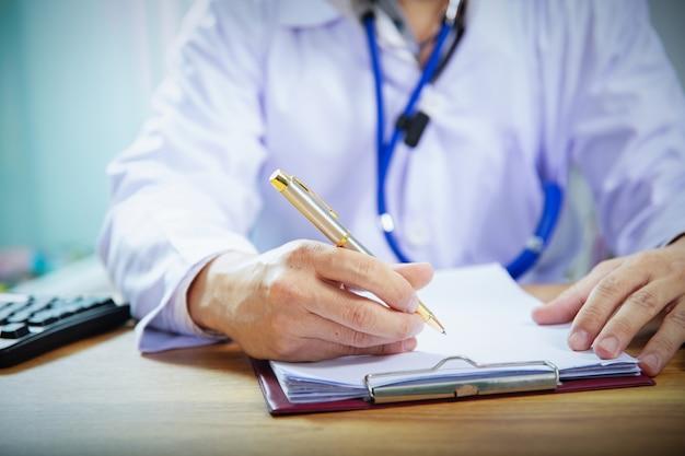 Le médecin prend des notes ou remplit la fiche médicale du client ou prescrit un médicament
