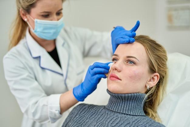 Médecin préparant une patiente pour la chirurgie esthétique en clinique