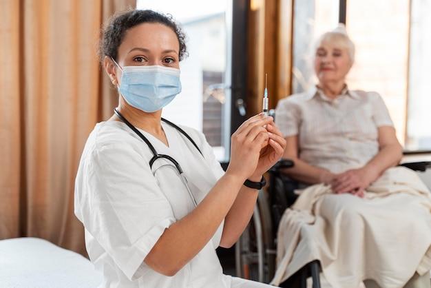 Médecin préparant le vaccin pour une femme âgée