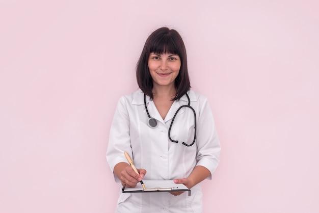 Médecin avec prescription sur presse-papiers isolé sur rose