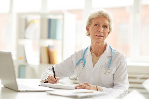 Médecin principal posant au bureau