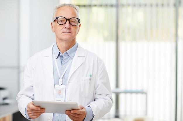 Médecin principal tenant une tablette numérique au bureau