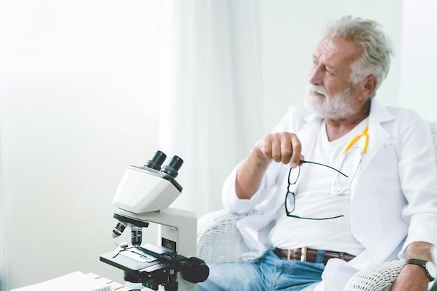 Médecin professionnel âgé pensant lointain regarder humeur sérieuse penser à des moyens de guérir le virus et la maladie de corona.