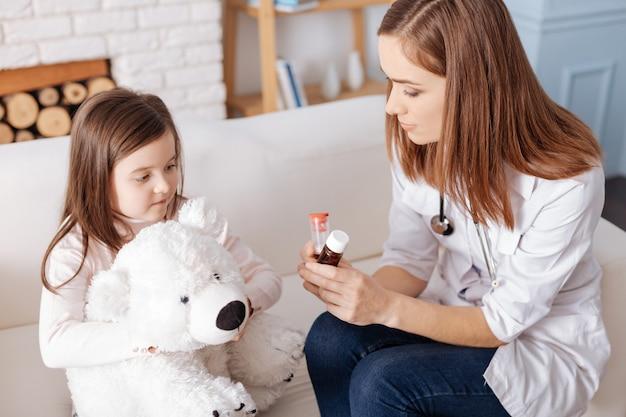 Médecin professionnel agréable tenant des pilules tout en donnant des conseils à la petite fille qui est assise avec son jouet moelleux