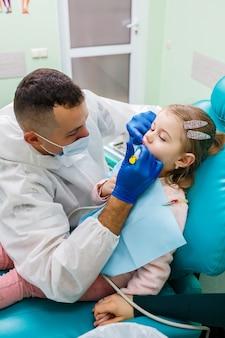 Un médecin professionnel, un dentiste pour enfants, soigne les dents d'une petite fille avec des instruments. cabinet dentaire pour l'examen des patients. le processus de traitement dentaire chez un enfant