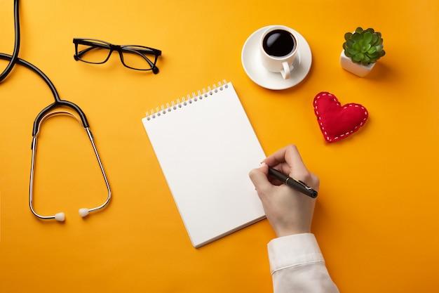 Médecin professionnel écrivant des dossiers médicaux dans un cahier avec stéthoscope, tasse à café et coeur